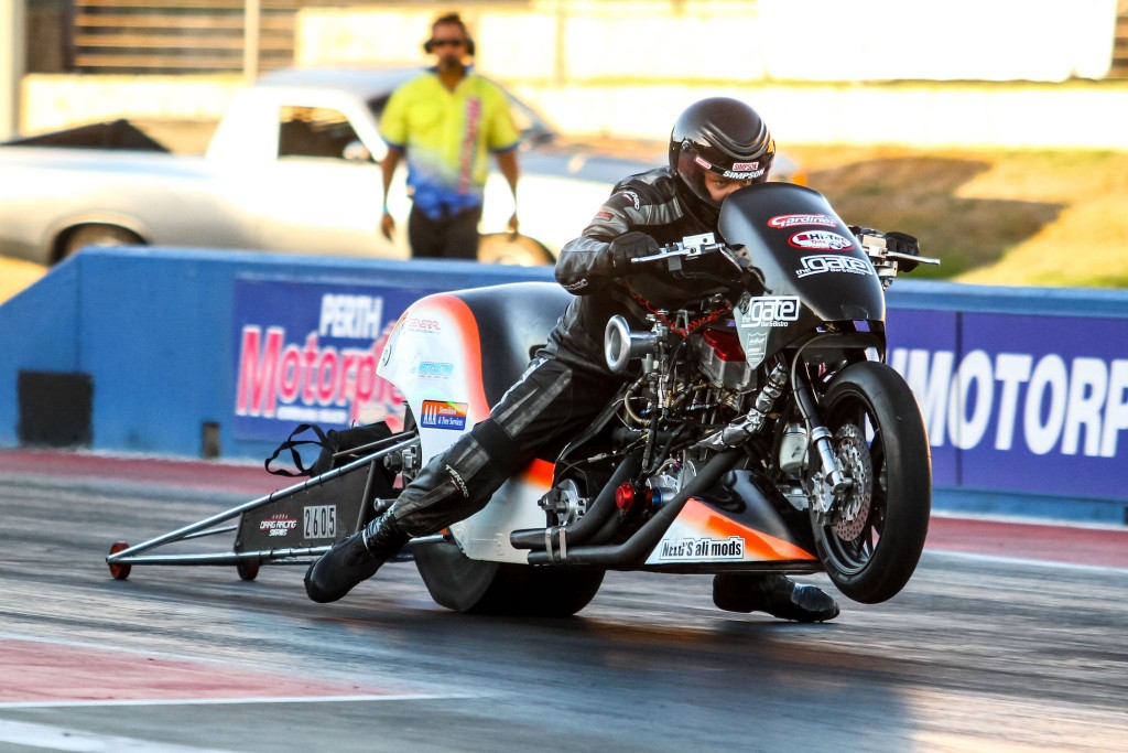 Benny Stevens carries the front wheel of his nitro-fuelled motorcycle at Perth Motorplex.